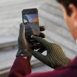 Green men's driving gloves with touchscreen technology.